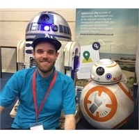 Image with Ayrden in a blue shirt smiling at the camera in front of a model BB8